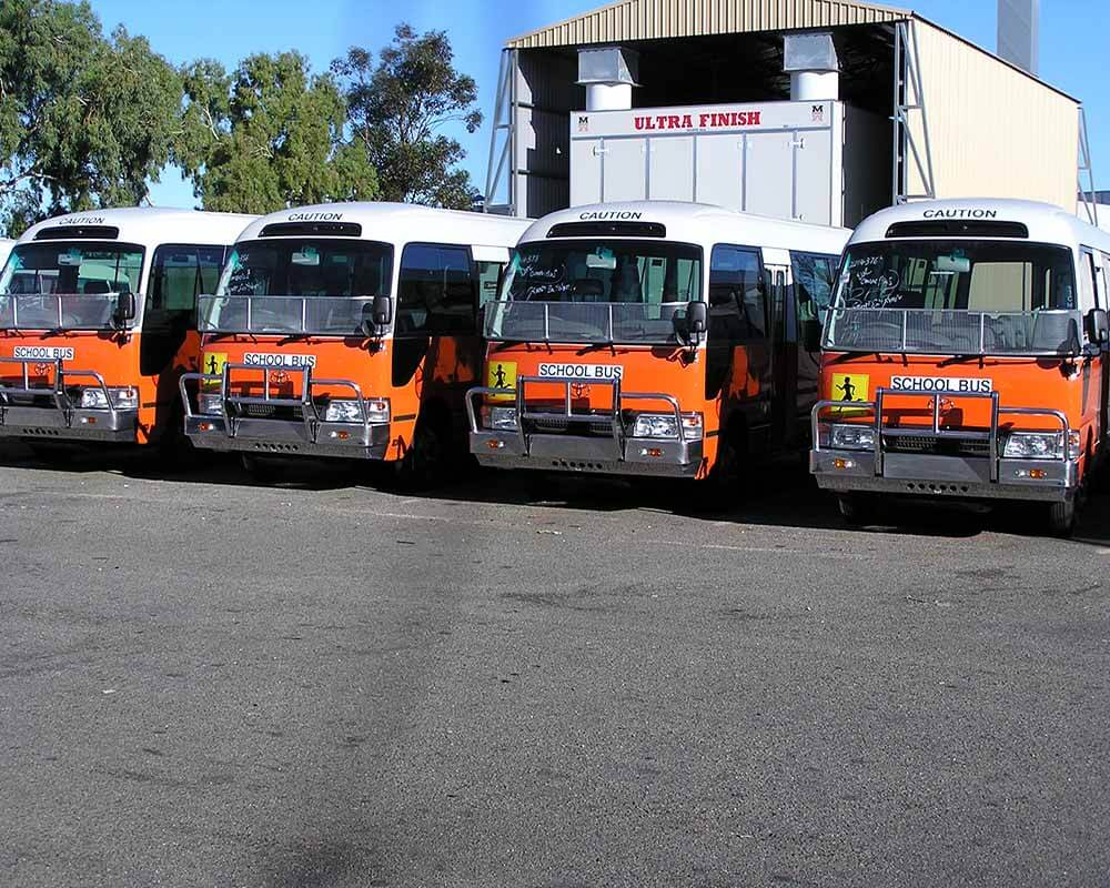 Toyota Coaster School bus conversions in front of paint booth